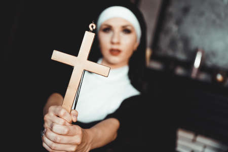 Nun holding a cross. The concept of religion. Young beautiful nun expels the devil