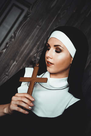 Sexy nun prays indoor . Beautiful young holy sister. Young beautiful nun with a cross in a robe in a black interior. Zdjęcie Seryjne