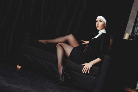 Sexy Nonne betet drinnen. Schöne junge heilige Schwester. Junge schöne Nonne mit einem Kreuz in einem Gewand in einem schwarzen Interieur.