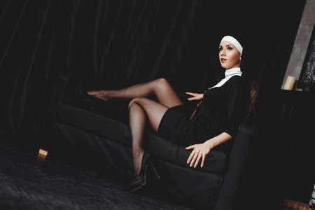 Sexy nun prays indoor . Beautiful young holy sister. Young beautiful nun with a cross in a robe in a black interior. 免版税图像