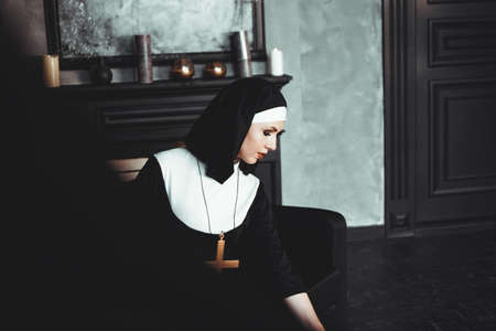 Sexy nun prays indoor . Beautiful young holy sister. Young beautiful nun with a cross in a robe in a black interior. Stock Photo