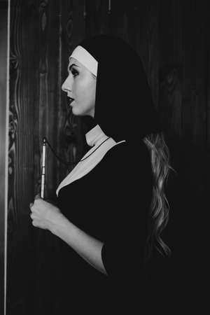Sexy nun prays indoor . Beautiful young holy sister. Young beautiful nun with a cross in a robe in a black interior. Black and white