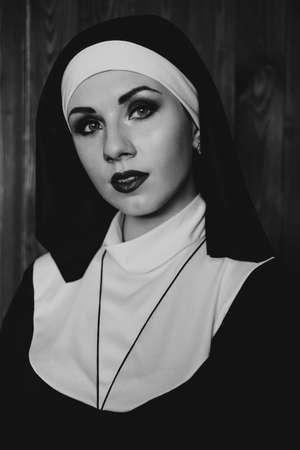 Sexy Nonne betet drinnen. Schöne junge heilige Schwester. Junge schöne Nonne mit einem Kreuz in einem Gewand in einem schwarzen Interieur. Schwarz und weiß