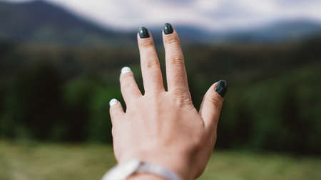 Hand against mountain. Female hand forward. Mountain valley. Natural summer landscape. Banco de Imagens