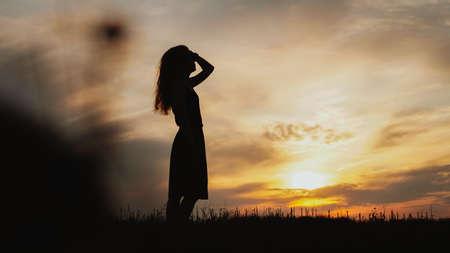 Silhouette di una giovane donna in piedi in un campo di erba secca su un tramonto luminoso Archivio Fotografico