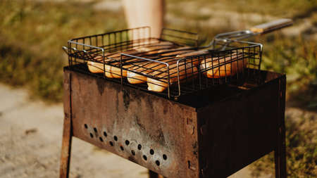 Delicious grilled sausages resting on the iron grid of a portable barbecue over glowing coals as they cook to perfection
