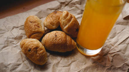 Freshly baked croissants with orange juice on kraft paper. Closeup photography of fresh delicious dessert for breakfast.