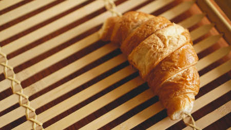 Fresh Croissant on rustic wooden background. Selective focus, horizontal.