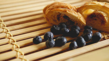 Delicious breakfast with fresh croissant and blueberry on wooden background