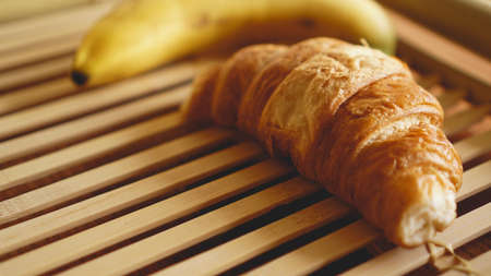 Banana and croissant on rustic wooden background. Selective focus, horizontal.