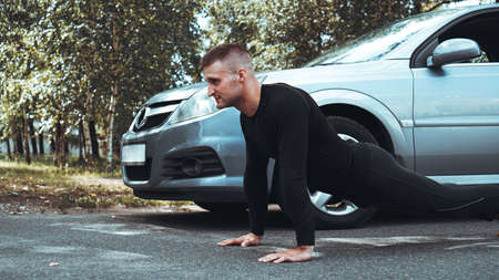 Handsome man near the car. The athlete wrung out next to the machine. Car VS man
