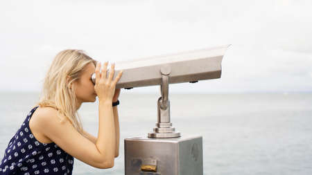 Woman standing on cruise liner deck and looking in binocular, half body, trawel time