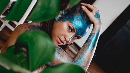 Portrait of a beautiful woman posing like in the wild forest. Woman with blue sparkles on her face. People are different from others. Individuality