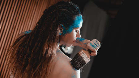Portrait of beautiful girl with blue facial bodyart with sequins. The artist draws body art on herself