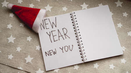 Text new year new you in the new year notebook on christmas background