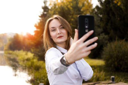 Portrait of cheerful young woman making selfie in park Banque d'images - 132553597