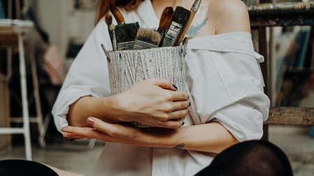 Closeup of female artist hand holding paintbrush at art workshop Stock Photo