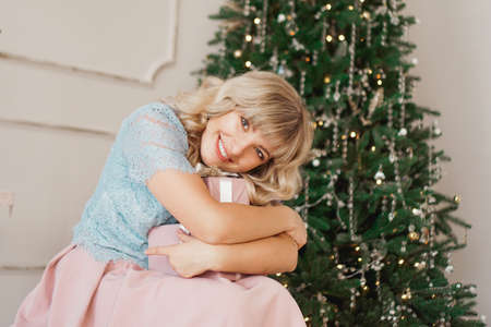 Lovely young woman with elegant style sitting indoor near decorated tree with pink Christmas presents Banco de Imagens