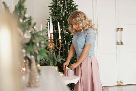 Cute positive woman near Christmas tree, opening gift in pink box Banco de Imagens