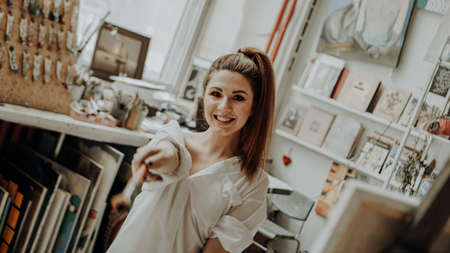 Portrait of happy smiling female artist with brush in art workshop. Selective focus. Vintage style photo Banco de Imagens