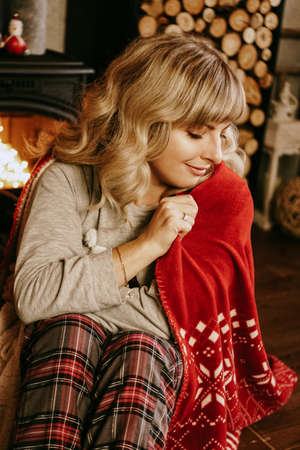 A beautiful young woman in a red plaid sits in a warm classic New Year interior 스톡 콘텐츠