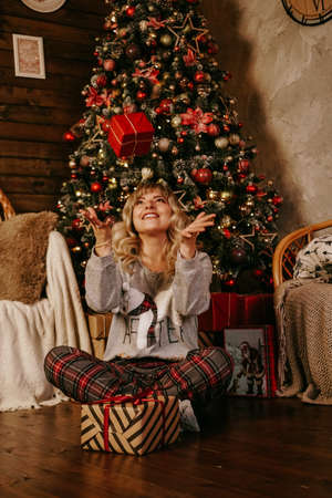 Woman throwing up a gift, concept of the new year, Christmas cozy interior 스톡 콘텐츠