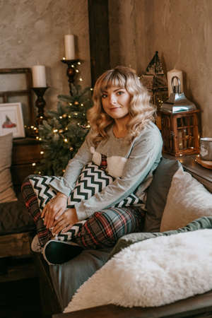 Close up portrait of beautiful young girl with long curly hair on a christmas background with lights. Magic warm new year photo. Cozy interior. 스톡 콘텐츠