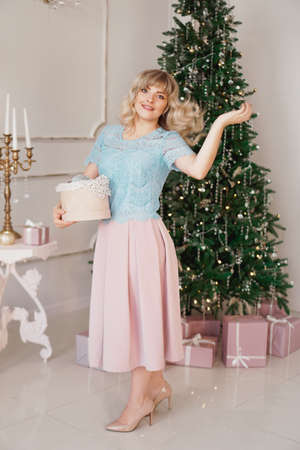 Young woman decorates Christmas tree with Christmas toys. Classic interior in white and gold