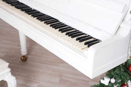 Keys on white upright piano with christmas decor with red balls Stock Photo