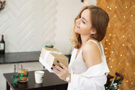 Beautiful girl dressed in a white shirt holding a gift in a modern bright kitchen