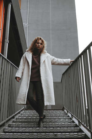 A girl with red curly hair in a white coat poses on the parking stairs. City Style - Urban Stockfoto