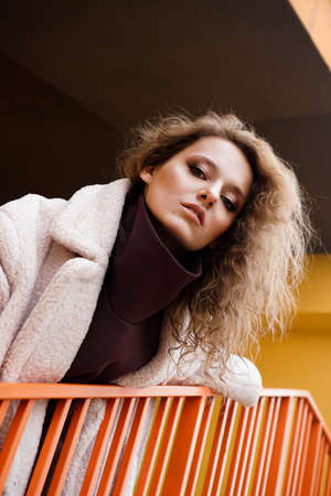A girl with red curly hair in a white coat poses on the yellow orange parking stairs. City Style - Urban