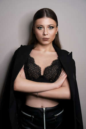 Beautiful young white girl close-up in a black jacket on a gray background. Make-up artist, beauty salon, magazine. Arms crossed. Vertical portrait.