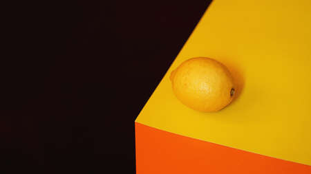 Fresh yellow lemon on black and orange material background Фото со стока