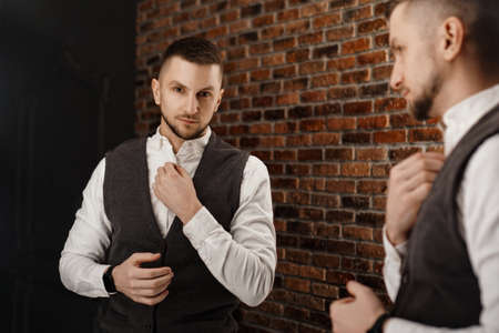 Stylish confident young man looking at himself in mirror. Fitting a suit in a store or sewing studio - loft interior