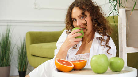 Young woman eating green apple at home. Healthy nutrition, diet food concept. Close-up portrait of beautiful young woman eating organic green apple.