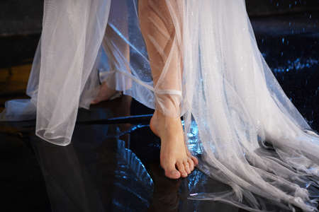 Beautiful female feet in the water with splashes. Photo in a neon light in the studio. White veil or long dress