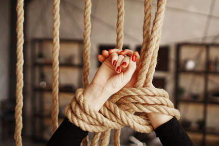 Tied with a rope female hands. Beautiful hands with red nails. Concept of or violence Stock Photo
