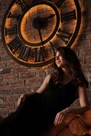 Young attractive woman under the clock, on brick wall background - loft style Banque d'images