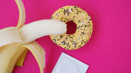 Banana, donut and condom. Sex idea. Bright picture on a pink background. The concept of health and protected