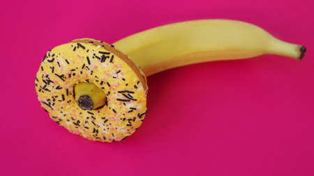 Sweet donut and banana on pink color background. Sex and Erotic concept