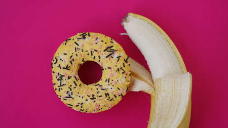 Sweet donut and banana on pink color background. Sex and Erotic concept. Banana hugs donut