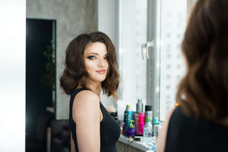 Portrait of elegant woman with curly hair looking at reflection in mirror. Beautiful brunette with bright makeup looks in the mirror Imagens