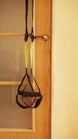 Closeup view of suspension on door on wooden background training at home - Fitness at home