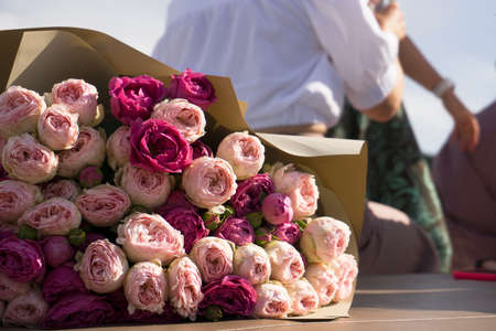 Colorful pink roses bouquet, soft and airy natural background with blurred people