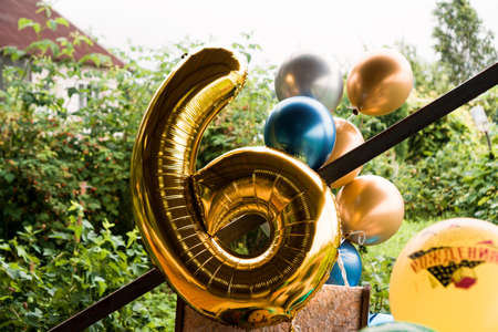 Composition of helium balloons gold and blue - large figure of six in gold color outside - blurred background