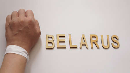 Fist. Hand with a white ribbon - a symbol of freedom in Belarus - vote 2020. The inscription Belarus on a white background