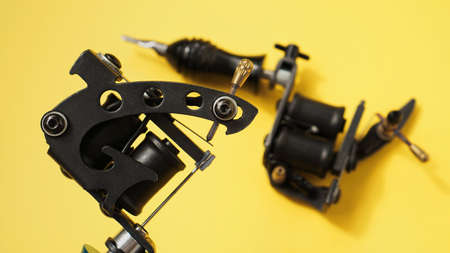 Two tattoo machines on a yellow background - tattoo industry
