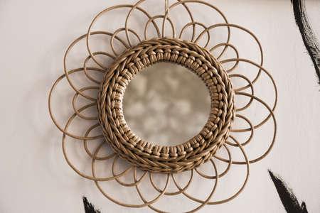 Vintage rattan mirrors on white textured wall. Round mirror with frame of eco straws