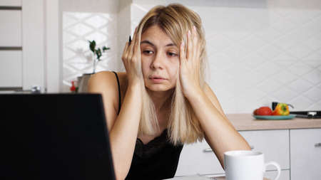 A businesswoman works at home or homeschooling a student using her laptop. Woman holding her head and worried about the problem